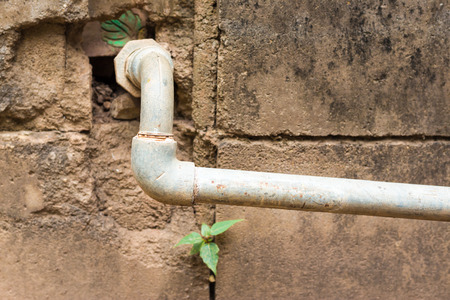 Metallic water pipe leading from an old brick-and-mortar wall photo