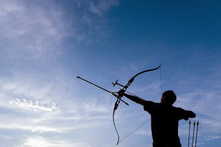 arco y flecha: Una silueta de un arquero dibujando su arco y apuntando hacia arriba con el cielo azul profundo y nubes blancas como fondo