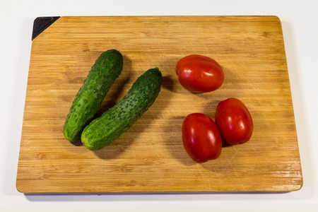 Vegetables cucumbers tomatoes on a wooden board