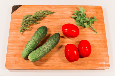 Vegetables cucumbers tomatoes sweet pepper parsley dill on a wooden board