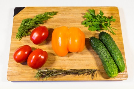 Vegetables cucumbers tomatoes sweet pepper parsley dill on a wooden board for you Stock Photo
