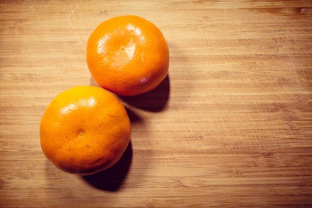 Two fresh tangerine not peeled on a wooden board. Vitamin C
