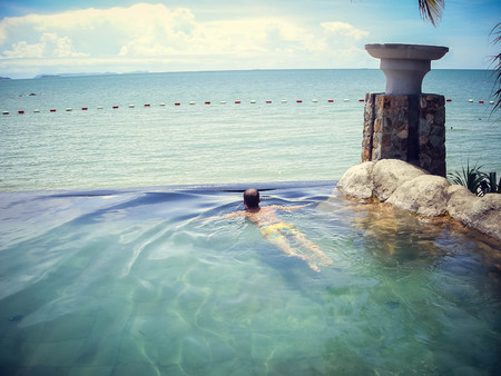 Guy tourist in the pool on the background of the ocean horizon in Thailand. Tourism.