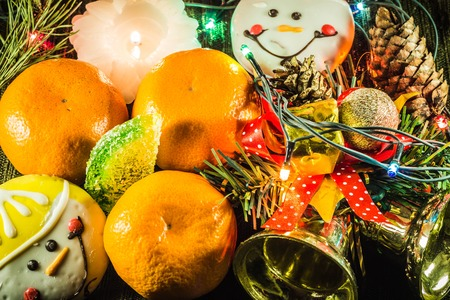 New Year decoration. Tangerines, candles, cookies, Christmas tree garland Happy NY Stock Photo