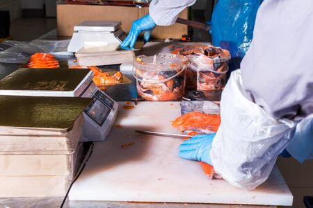 Fish production. Worker cuts fish with a knife into pieces