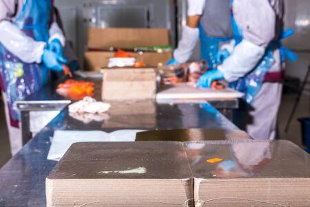 Production de poisson. Le travailleur étale des morceaux de poisson sur l'emballage