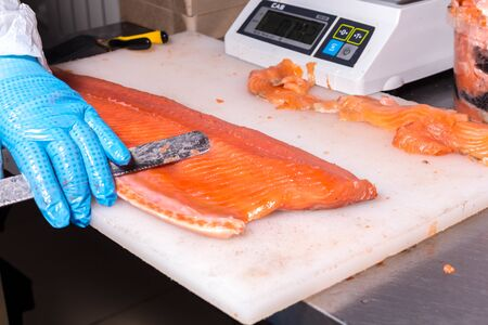 Fish production. A worker removes excess fat with a knife from a fish
