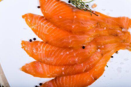 Il pesce rosso affettato a fette giace su un piatto bianco. Intorno alle verdure Archivio Fotografico