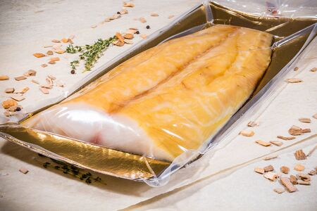 White smoked fish in a sealed vacuum package on the background of chips