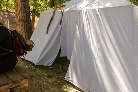 Military tent made of white matter in the field. On the ground