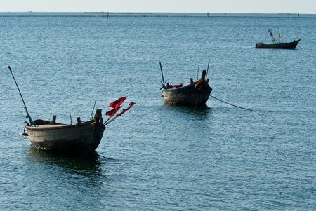 Three boat stand by on sea photo