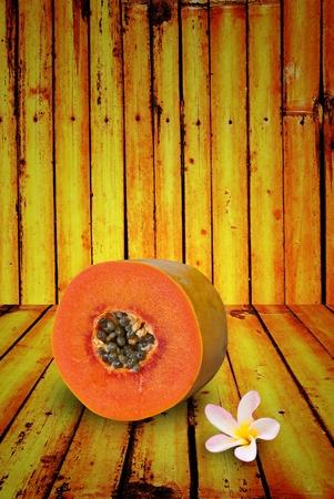 leelawadee: Papaya matured and leelawadee flower on gradient bamboo Stock Photo