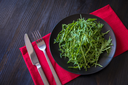 rucola: fresh rucola leaves on black plate