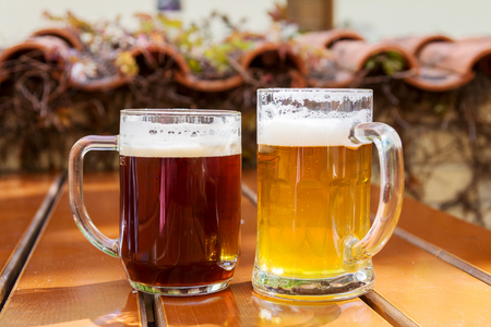 bleb: two mugs of beer on a table at an outdoor cafe