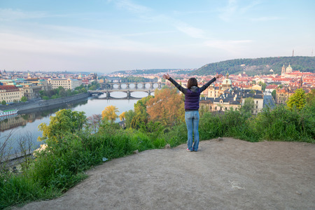 pavilon: young woman with hands up on the hill over Vltava river and bridges of Prague