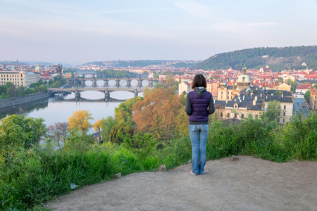 pavilon: young woman looking at the Vltava river and bridges of Prague
