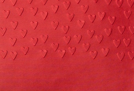 Background of red paper with embossed hearts