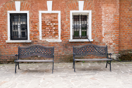 two benches on the background of an old brick wall