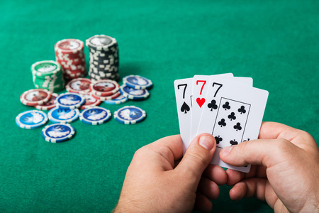 lear: chips and cards for poker in hand on green table  Stock Photo