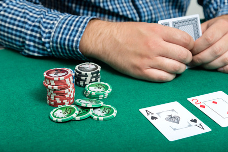 chips and cards for poker in hand on green table  Stock Photo