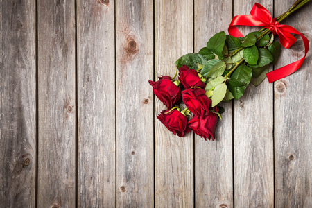 bouquet of red roses with bow on wood background. Valentines Day background