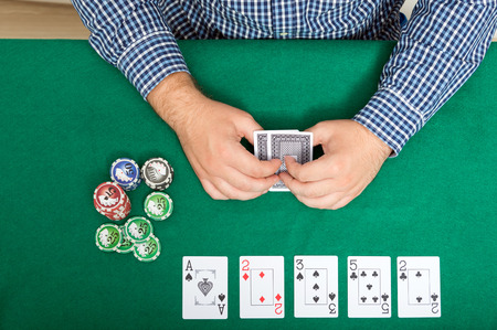 lear: chips and cards for poker in hand on green table, top view