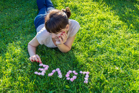 smiling girl puts the word Love of rose buds on green grass