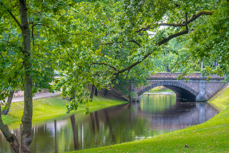 beautiful city park with river and bridge in summer day  Stock Photo