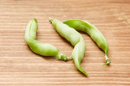 Ugly organic home grown pea on wooden background. Food waste concept. Top view.