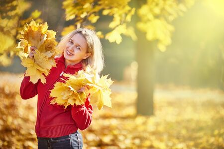 Lady posing with leaves autumnal nature background. Girl blonde makeup dreamy face hold bunch fallen maple yellow leaves. Autumnal concept. Woman spend pleasant time in autumnal park. space for text.