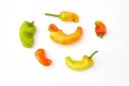 Trendy ugly organic fruits and vegetables. peppers on white background. Misshapen produce, deformed fruits and vegetables, food waste concept. Top view, flatlay.