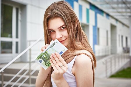 young dark-haired girl holding a bundle of euro banknotes in her hands Stok Fotoğraf