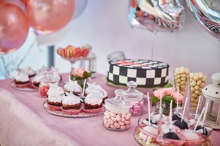 beautiful pink candy bar with cupcakes, pops, cake, marshmallows dragees. balloons around Stock Photo