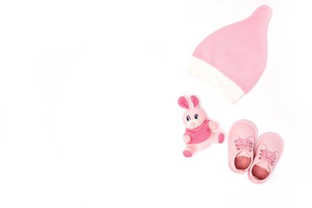 pink hat, toy and shoes for babies top view. copy space. horizontal image.