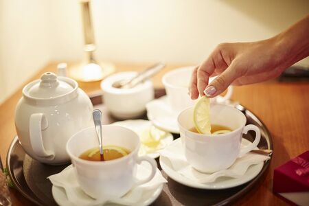 life style. female hand with beautiful nails with french manicure, puts a lemon in a cup with tea.