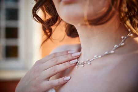 beautiful nails on the hand that touches the necklace on the girls neck.