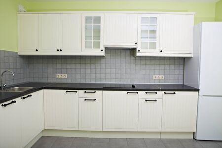 moderne weiße Küche in der Wohnung. Kühlschrank, Herd, Spüle Wasserhahn. Standard-Bild