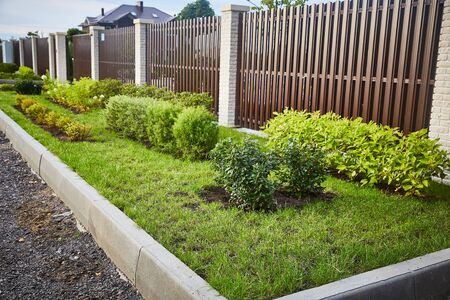 brown fence with decorative flower beds and a border stone