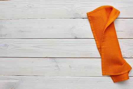 Orange dishcloth on white wooden boards. copyspace. Stock Photo