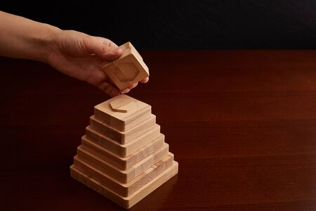 Toy made of beech wood. manual work on the cnc machine. pyramid with geometric shapes. Development and parenting and entertainment of parents. Stock Photo