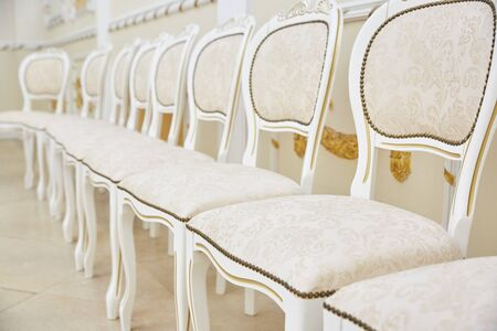 A row of white chairs of classic design in a bright room. rag seat and backrest. nobody Zdjęcie Seryjne