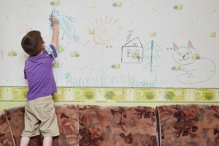 Niño de 5 años dibuja en la pared de la habitación.