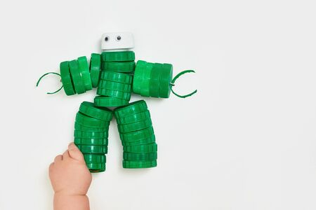 Zero waste, the second life of things. Toy robot made of plastic caps on a white background. faceless. Recycling art. Copyspace.