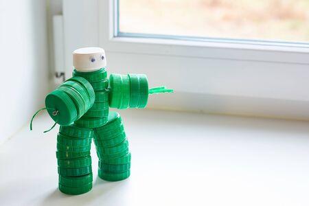 Recyclingkunst. Zero Waste, das zweite Leben der Dinge. Spielzeugroboter aus Plastikkappen am Fenster. Exemplar. Standard-Bild