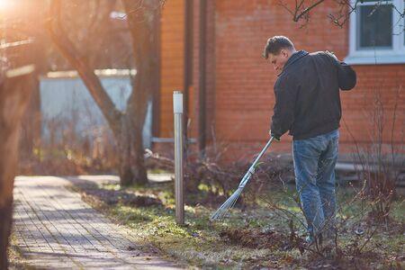 Gardener raking fall leaves in garden. Copy space. Zdjęcie Seryjne