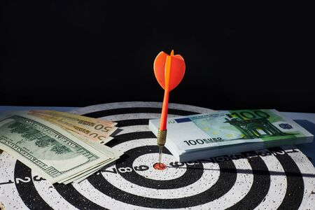 Business concept of money and goal achievement. Darts, cash banknotes dollars and euros. Black background for text.