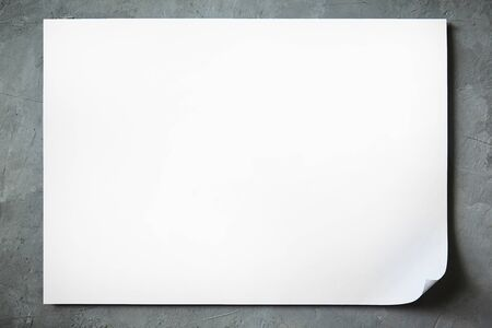 mock up of a sheet of white A4 paper with a bent corner and shadow on a concrete background