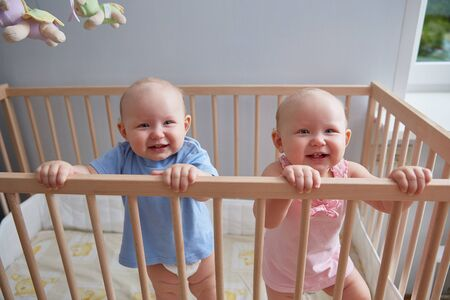 Children twins boy and girl are smiling while standing in the crib