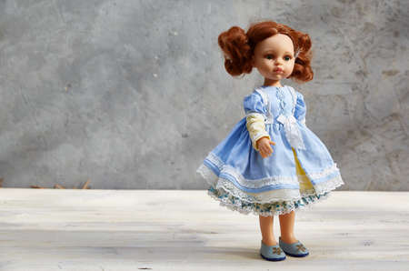 doll in a yellow and blue dress, on a gray concrete background. copy space Archivio Fotografico