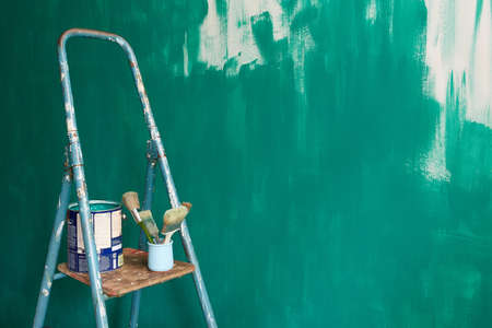 Stepladder, brushes and paint on the background of a green unpainted wall.